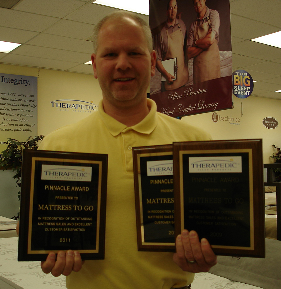 Jeff Scheuer holds three Therapedic Pinnacle Awards won by Mattress To Go.